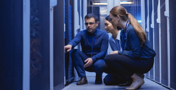Male and female IT engineers checking servers in server room.