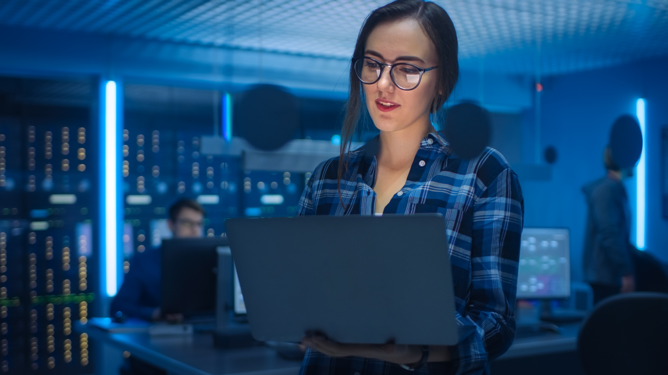 Portrait of a Smart Seductive Young Woman Wearing Glasses Holds Laptop. In the Background Technical Department Office with Specialists Working and Functional Data Server Racks